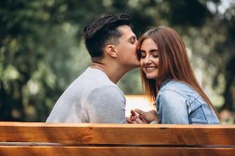 Junge Paare, die auf Bank im Park sitzen