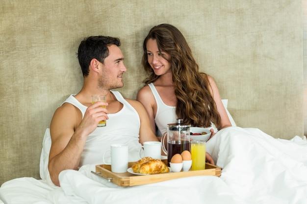 Junge paare, die auf bett im schlafzimmer frühstücken