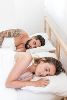 Junge paare, die auf bett schlafen