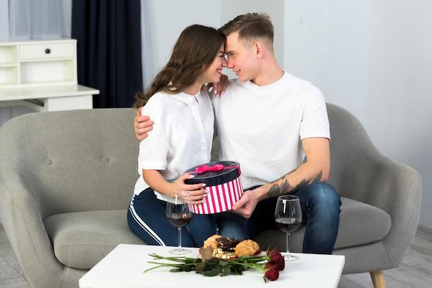 Junge paare, die auf couch mit geschenkbox sitzen