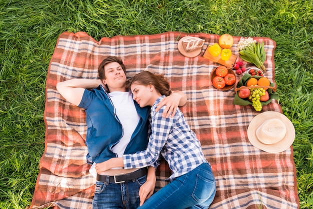 Junge paare, die auf decke während des picknicks streicheln