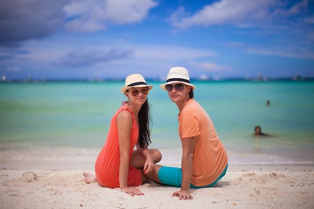 Junge paare, die auf einem tropischen strand sich amüsieren und kamera betrachten