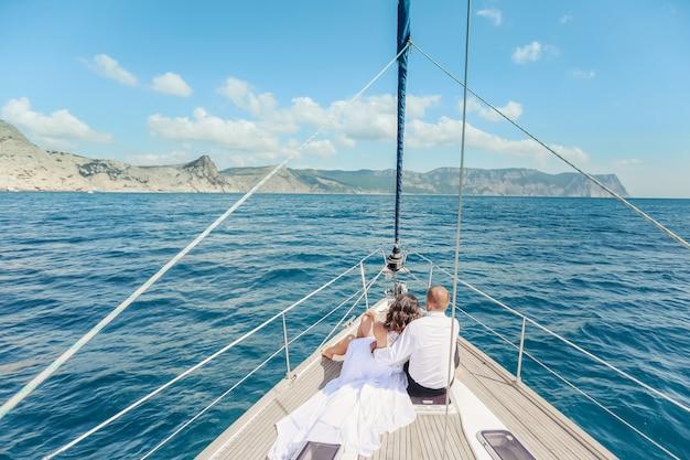 Junge paare, die auf einer yacht sich entspannen.