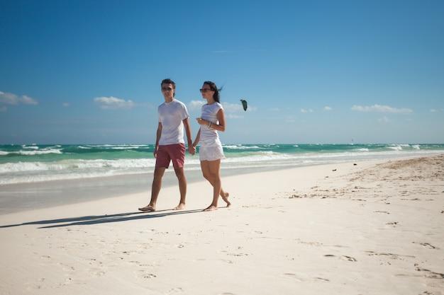 Junge paare, die auf exotischen strand am sonnigen tag gehen