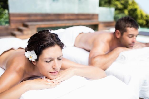Junge paare, die auf massagetabelle im badekurort sich entspannen