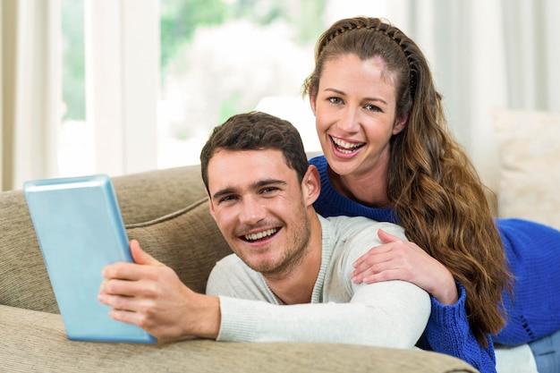 Junge paare, die auf sofa sitzen und tablette im wohnzimmer verwenden