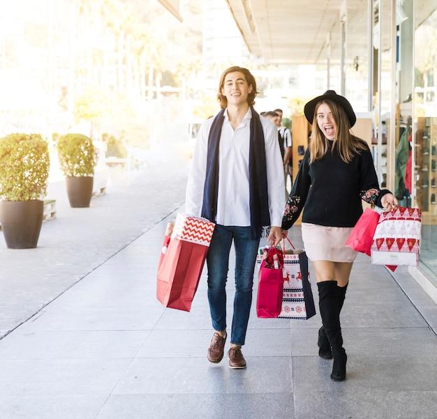 Junge paare, die auf straße mit einkaufstaschen gehen