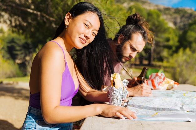 Junge paare, die bei tisch mit karte und snack sitzen