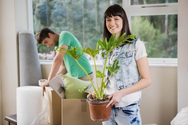 Junge paare, die beim auspacken von kartonkästen im neuen haus sich unterstützen