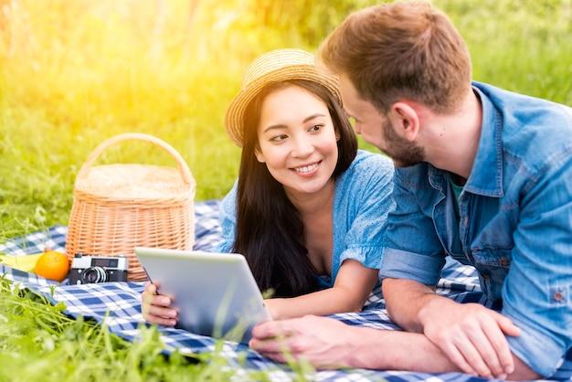 Junge paare, die beim halten der tablette auf picknick an einander lächeln