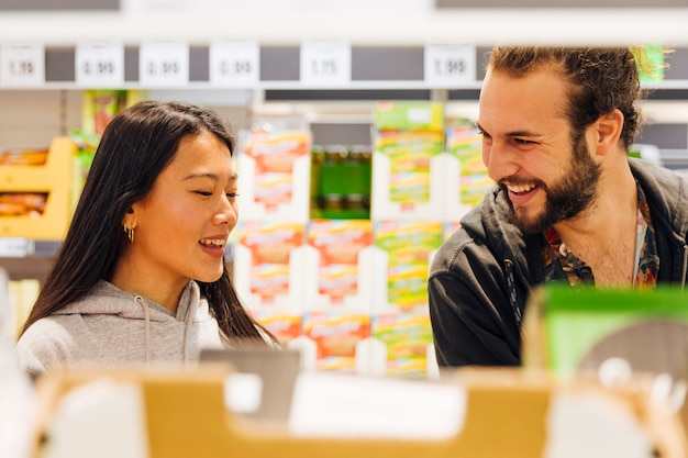 Junge paare, die das einkaufen im supermarkt tun