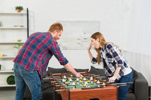Junge paare, die das fußballtischfußballspiel im wohnzimmer spielen