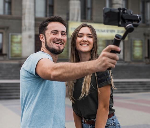 Junge paare, die draußen ein selfie nehmen