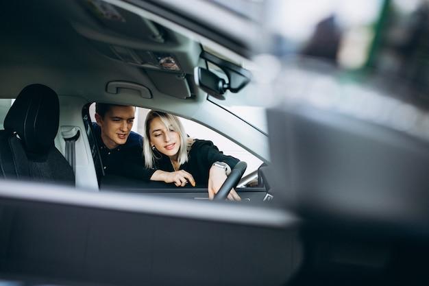 Junge paare, die ein auto in einem autoshowraum wählen
