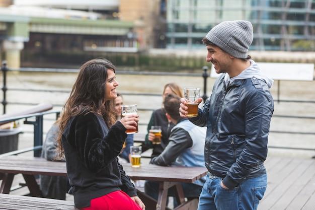 Junge paare, die ein bier an der kneipe in london genießen.