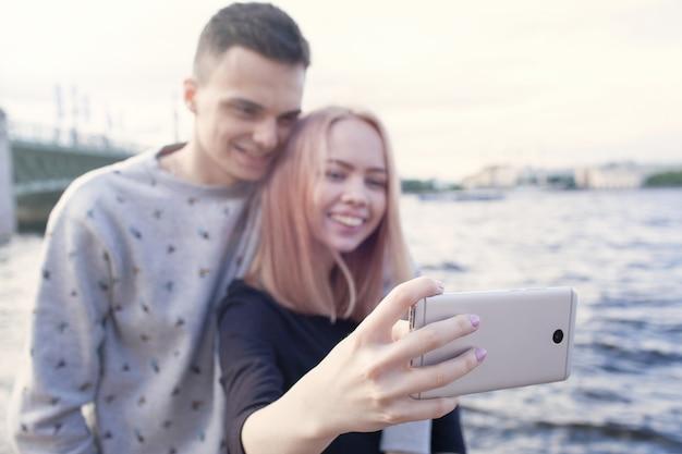 Junge paare, die ein selfie mit smartphone fotografieren.