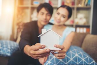 Junge Paare, die ein weißes Miniaturhaus im Wohnzimmer halten