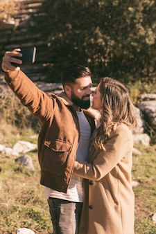 Junge paare, die einander betrachten und ein selfie nehmen