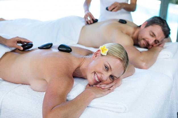 Junge paare, die eine heiße steinmassage vom masseur empfangen