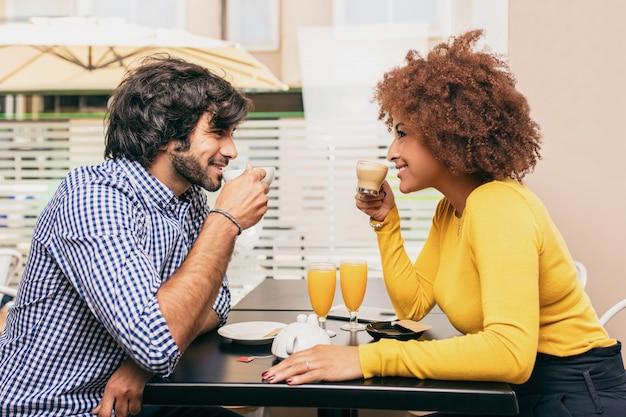 Junge paare, die einen kaffee am café trinken. sie lächeln und schauen sich an