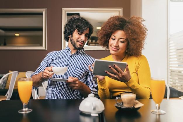 Junge paare, die einen kaffee und einen orangensaft am café, unter verwendung einer tablette trinken