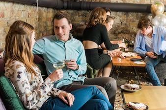 Junge Paare, die Getränke an der Party haben