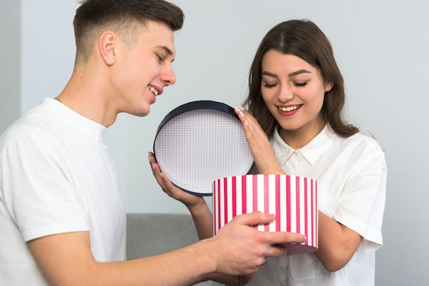 Junge paare, die große geschenkbox auf couch öffnen