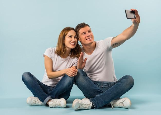 Junge paare, die ihre hand wellenartig bewegt, die selfie auf smartphone gegen blauen hintergrund nimmt