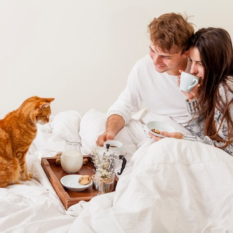 Junge paare, die im bett frühstücken