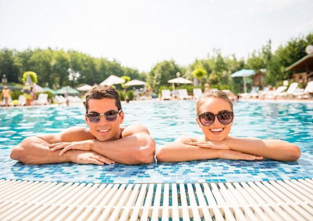 Junge paare, die im erholungsortswimmingpool sich entspannen.