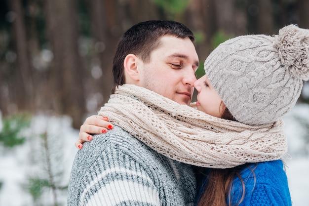 Junge paare, die im wald im winter umarmen und küssen.