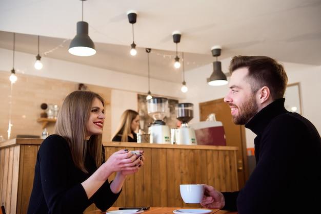 Junge paare, die in einer kaffeestube sprechen