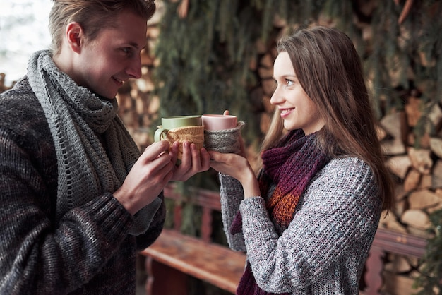 Junge paare, die in einer romantischen kabine draußen im winter frühstücken. winterurlaub und ferien