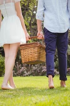 Junge paare, die in garten mit picknickkorb gehen