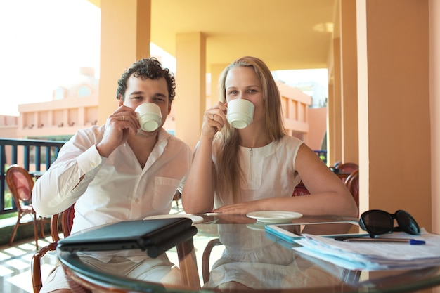 Junge paare, die kaffee auf einem balkon trinken