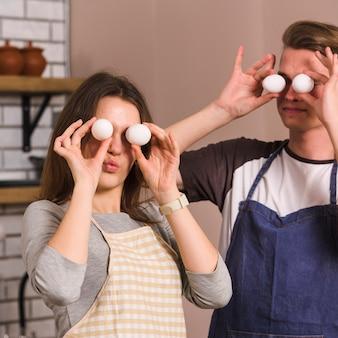 Junge paare, die lustige gesichter mit eiern in der küche bilden