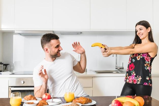 Junge paare, die mit banane in der küche spielen