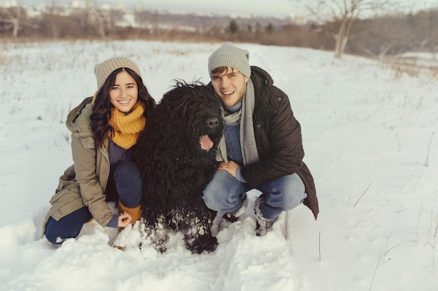 Junge paare, die mit einem hund an einem wintertag gehen