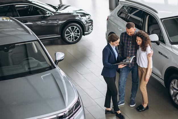 Junge paare, die mit einem verkäufer in einem autosalon sprechen