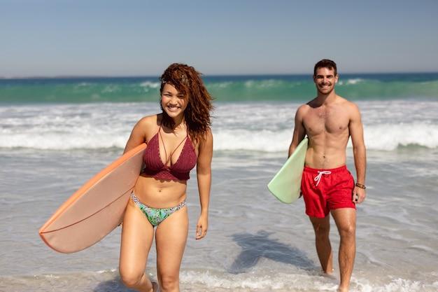 Junge paare, die mit surfbrett auf strand im sonnenschein gehen