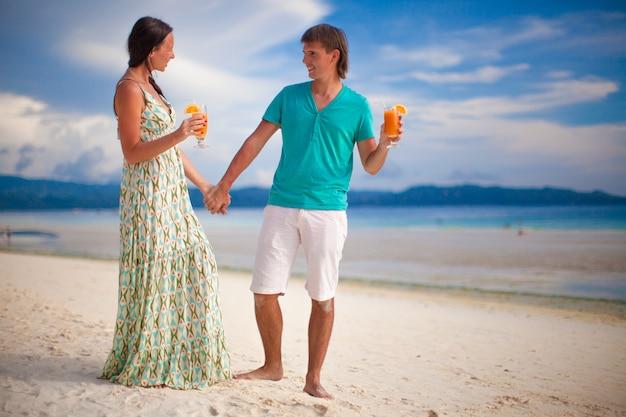 Junge paare, die mit zwei cocktails auf sandigem strand sich entspannen