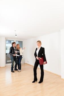 Junge paare, die nach immobilien mit weiblichem grundstücksmakler suchen