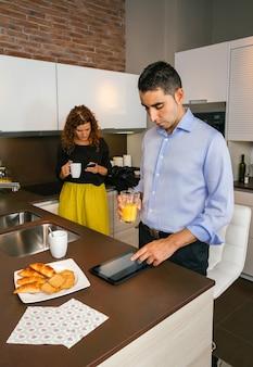 Junge paare, die nachrichten in ihren elektronischen geräten suchen, während sie zu hause schnell frühstücken, bevor sie zur arbeit gehen