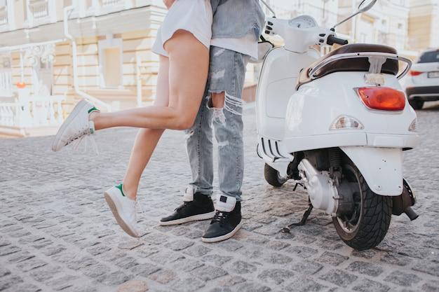 Junge paare, die nahe einem motorrad umarmen