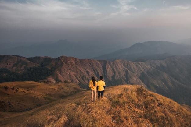 Junge paare, die reisende gelbe hemden wandern, die in der mitte einer goldenen wiesenbergansicht stehen. in mulayit taung in myanmar.