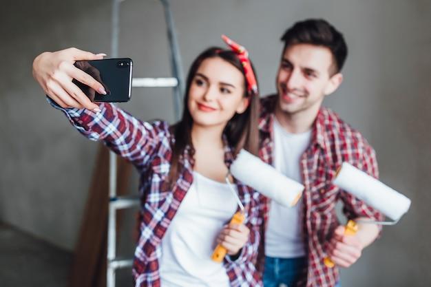 Junge paare, die reparaturen in der wohnung tun und fotos von selbst am telefon machen