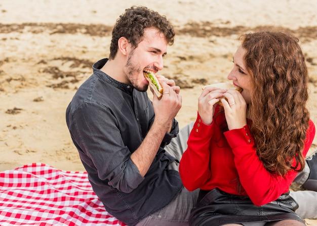 Junge paare, die sandwiche auf karierter bettdecke essen