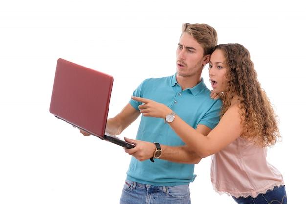 Junge paare, die schlechte nachrichten auf ihrem laptop lokalisiert auf weißem hintergrund empfangen