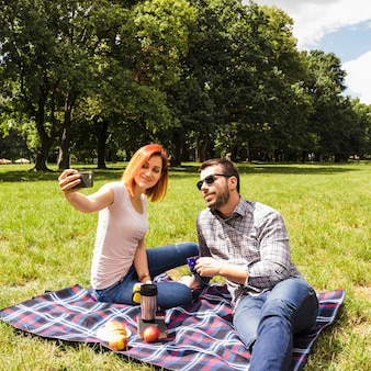 Junge paare, die selfie am handy picknick am im freien nehmen