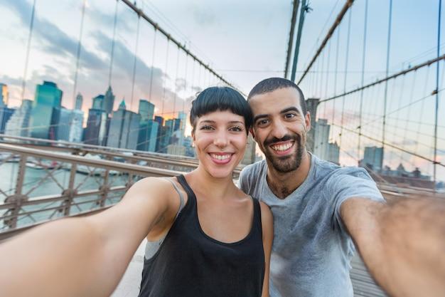 Junge paare, die selfie auf brooklyn-brücke nehmen